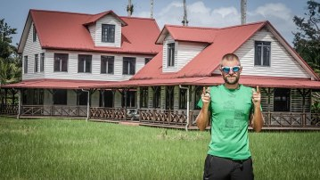 Blonde man with sunglasses in front of a house in Paramaribo,Surinamec