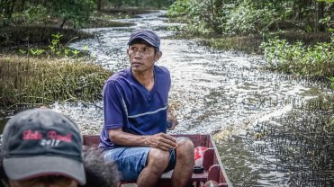 a man sitting on a boat in a swamp