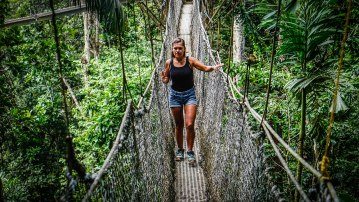 A female brunette traveler walking over a Suspension bridge