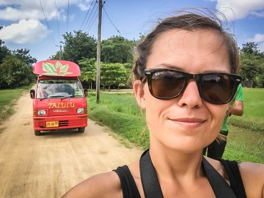 Selfie of a woman and in the background a Tuk Tuk in Paramaribo