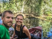 a smiling man and woman on a boat in a swamp