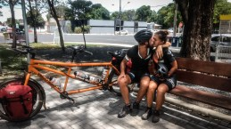 man and woman sitting on a bench next to tandem bicycle in Boa Vista, North of Brazil