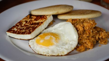 two arepas egg and cheese on a plate in Venezuela