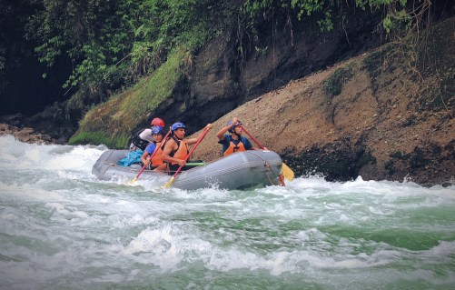 four people rafting in white water
