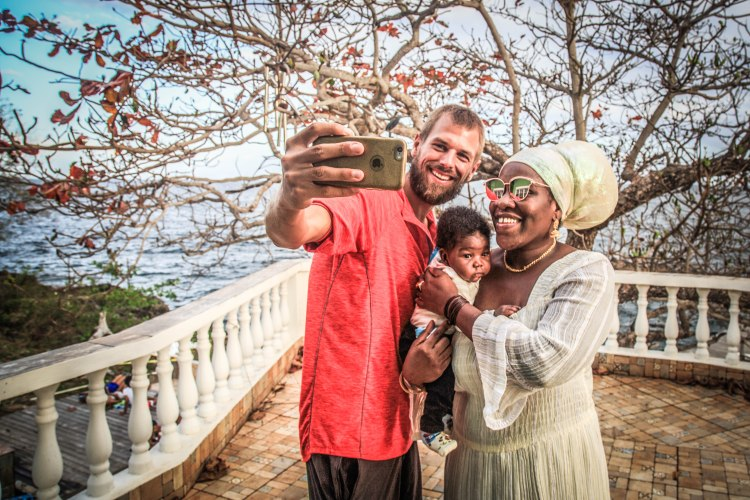 a selfie of a blonde guy and a black women with her baby