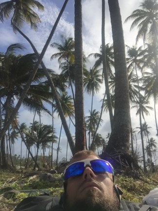 A blonde bearded man wearing sunglasses laying on a sandy beach underneath palm trees in Trinidad
