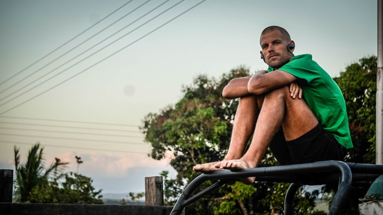 Man sitting on a wracked car in Venezuela