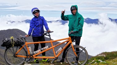 a man and a women on a tandem bicycle in the mountains / Cycling through South America