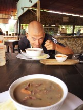 A bold man eating a soup in South America