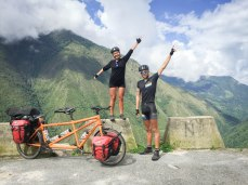 a happy couple next to a tandem bicycle in the mountains / Cycling through South America