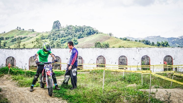 man on a motocross bike and another man next to him in Colombia