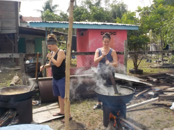 two peace corp woman making food