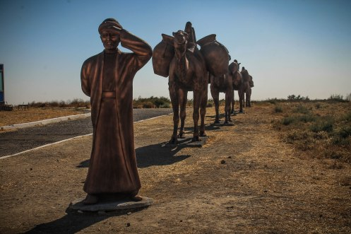 A stature of a man and three camels