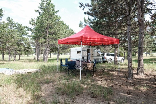 A Jeep with a camper van next to a red shelter