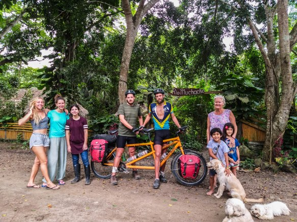 Picture of 4 woman,2 children, 3 dogs and 2 men on a tandem bicycle in Ecuador