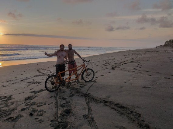Two men holding a tandem bicycle on the beach during sunset in Ecuador