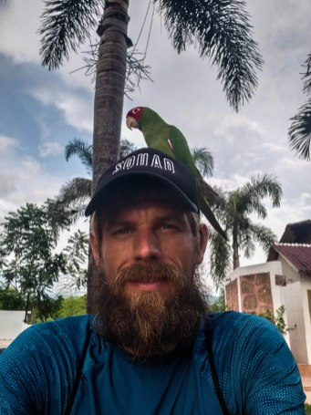 Bearded man with a perrot on his head