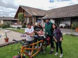 three men, a woman and a baby next to a tandem bicycle at the Quinta Samai in Ecuador