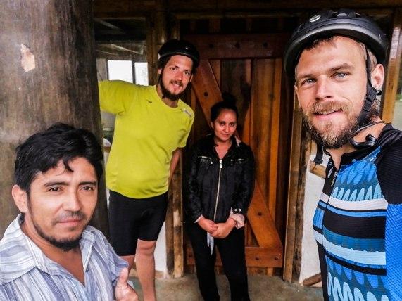 Selfie of 3 men and a woman in front of a door, in Ecuador