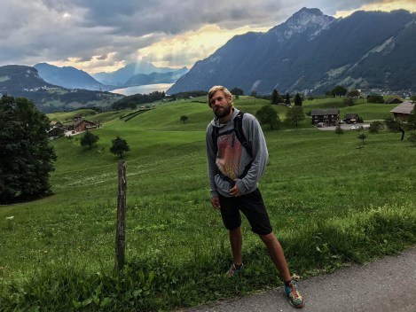 A blonde man wearing black shorts and a hoodie, is hiking in front of a meadow and a mountain lake