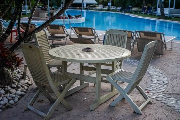 four chairs, a table and loungers by a swimming pool