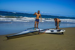 two blonde man next to two surfboard at the beach