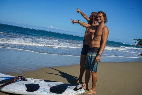two topless man pointing at the sea next to a surfboard