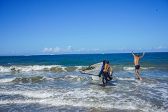 two man in the sea, one of them carrying a windsurf board