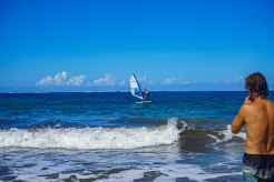 man on on the sea looking at another man windsurfing