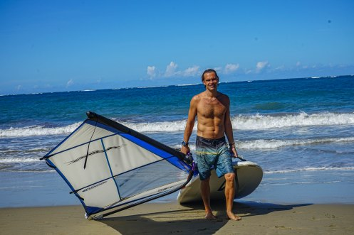 man carrying a wind surf board on the beach