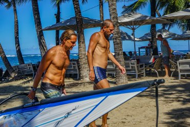 a man carrying a windsurfing board and a man walking on the beach