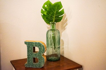 a big B and a plant in a vase in Orange B Living