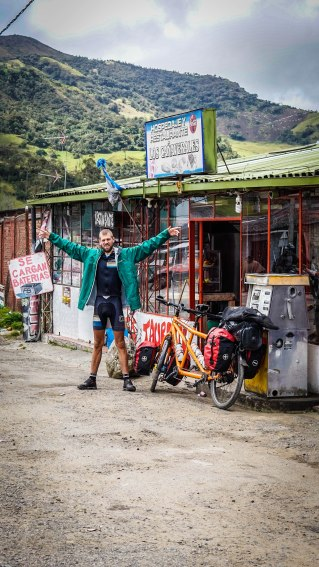 A bicycle rider stretching his arms next to a orange tandem bicycle in front of a shop in the mountains