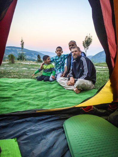 view outside of a tent on two boys and two man, in the background the countryside of Kosovo