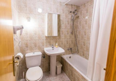 Bathroom with bathtub, bidet, toilet, hair dryer, mirror cabinet, sink