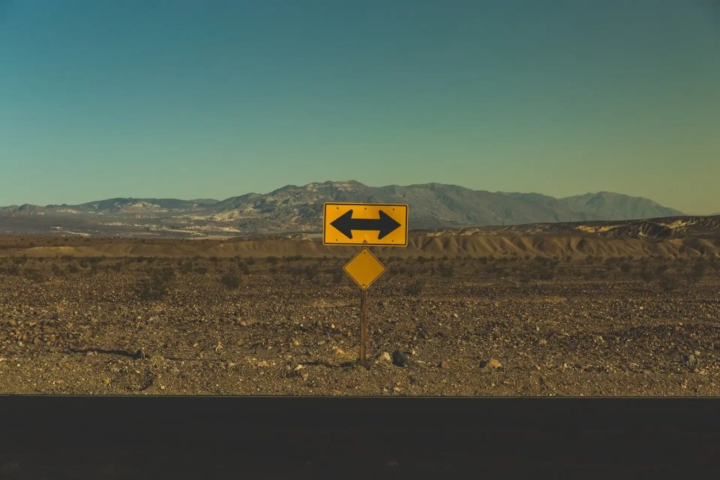 A yellow directional sign with arrows pointing to the left and the road stands in a gravel field with mountains in the background.