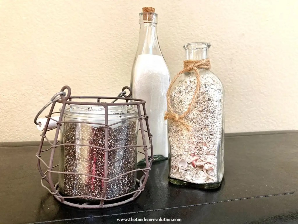 A jar containing black sand, a jar containing white sand, and a jar containing small beach rocks placed near each other on a bench.