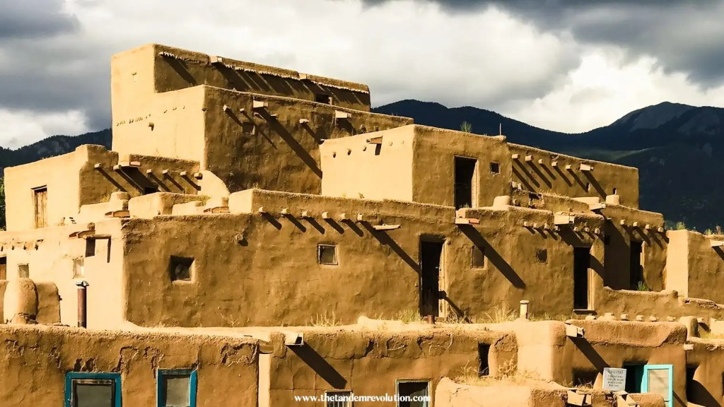The Native American village of Taos, New Mexico looms in the foreground with mountains in the background and clouds in the sky.