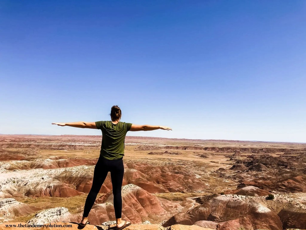 A woman stretches her arms out horizontally over a view of white-topped red hills in a valley at Petrified Forest National Park.
