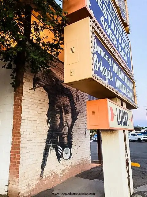 A Native American and an eagle are painted on a brick wall next to a hotel lobby sign in Gallup, New Mexico.