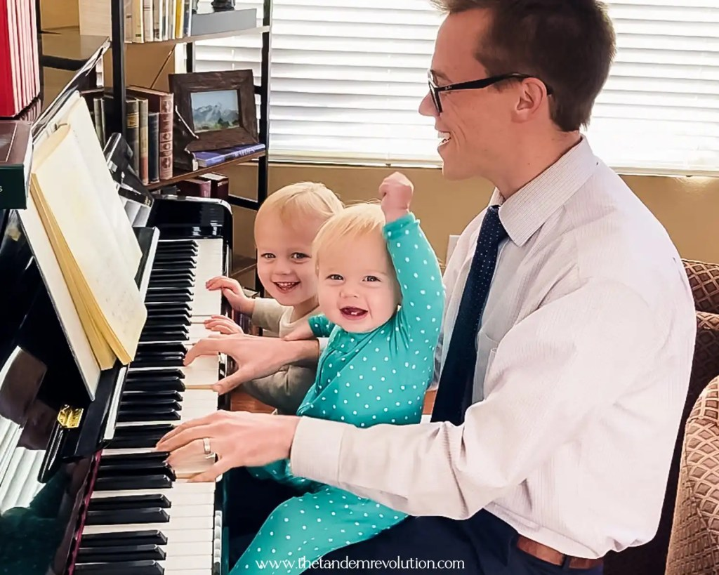 Two kids and a dad playing piano and smiling