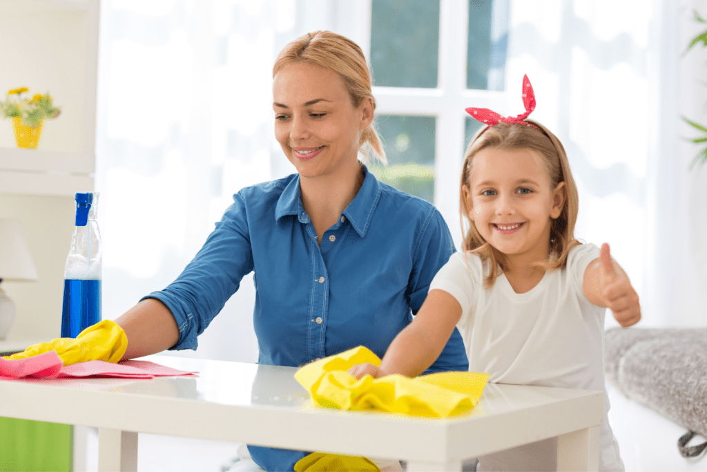 Young girl giving thumbs up while cleaning counter with her mom