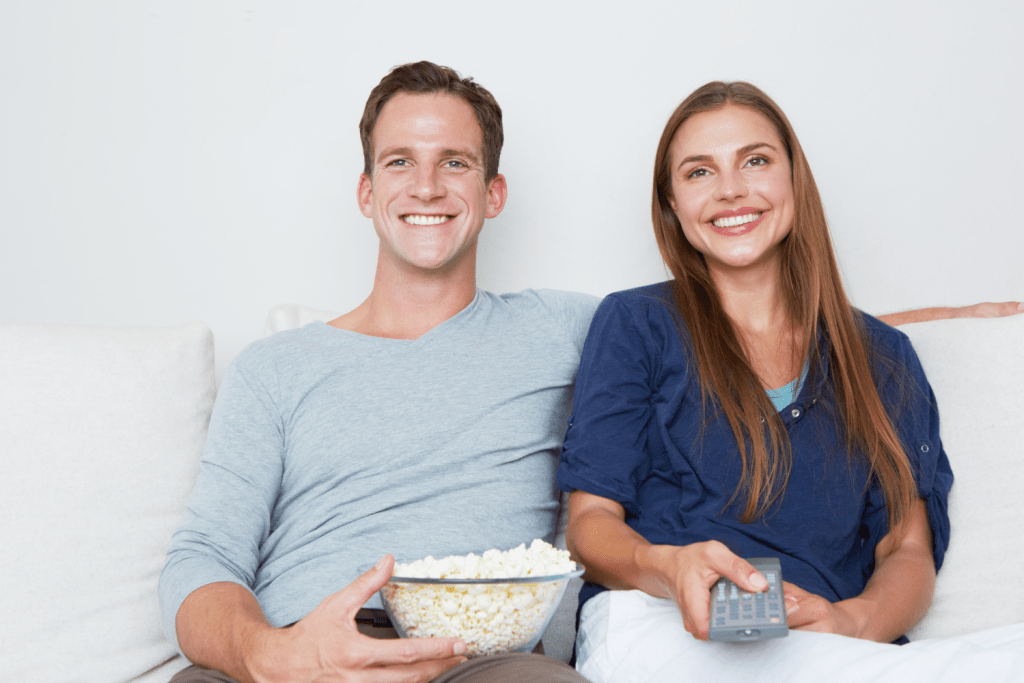 A husband and wife watch television together while eating popcorn.