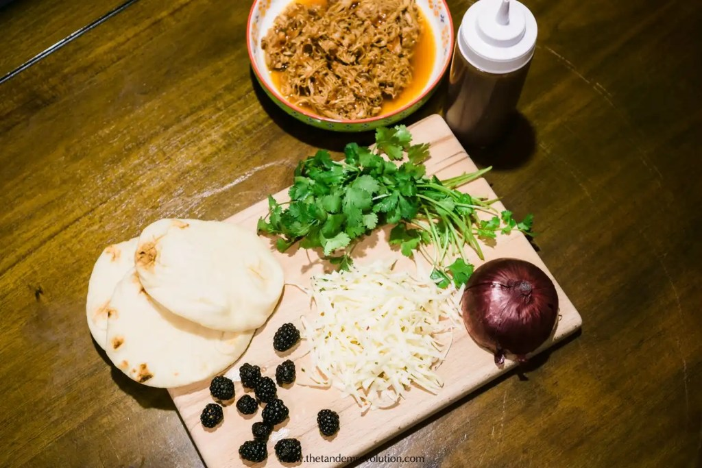 BBQ chicken, BBQ sauce, Indian naan bread, cilantro, grated cheese, blackberries, and an onion laid out on a wooden cutting board.