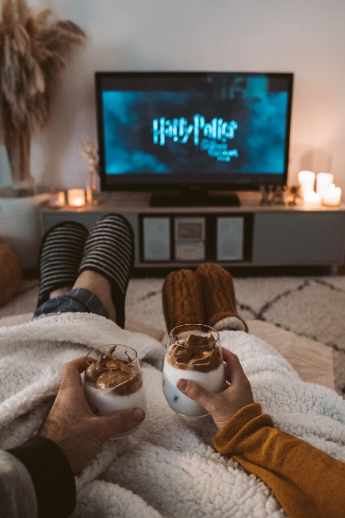 A couple sitting on the couch spending time together by watching a favorite movie with hot chocolate