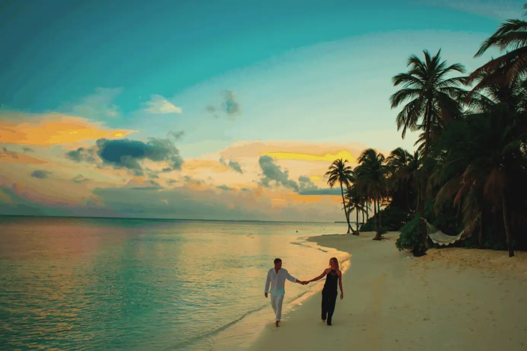 A couple walking along  beach in paradise next to the ocean