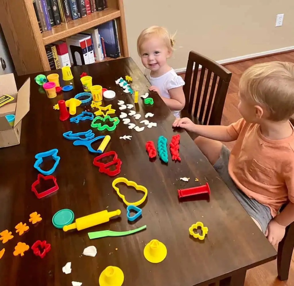 Two young toddlers playing with playdo at a craft table