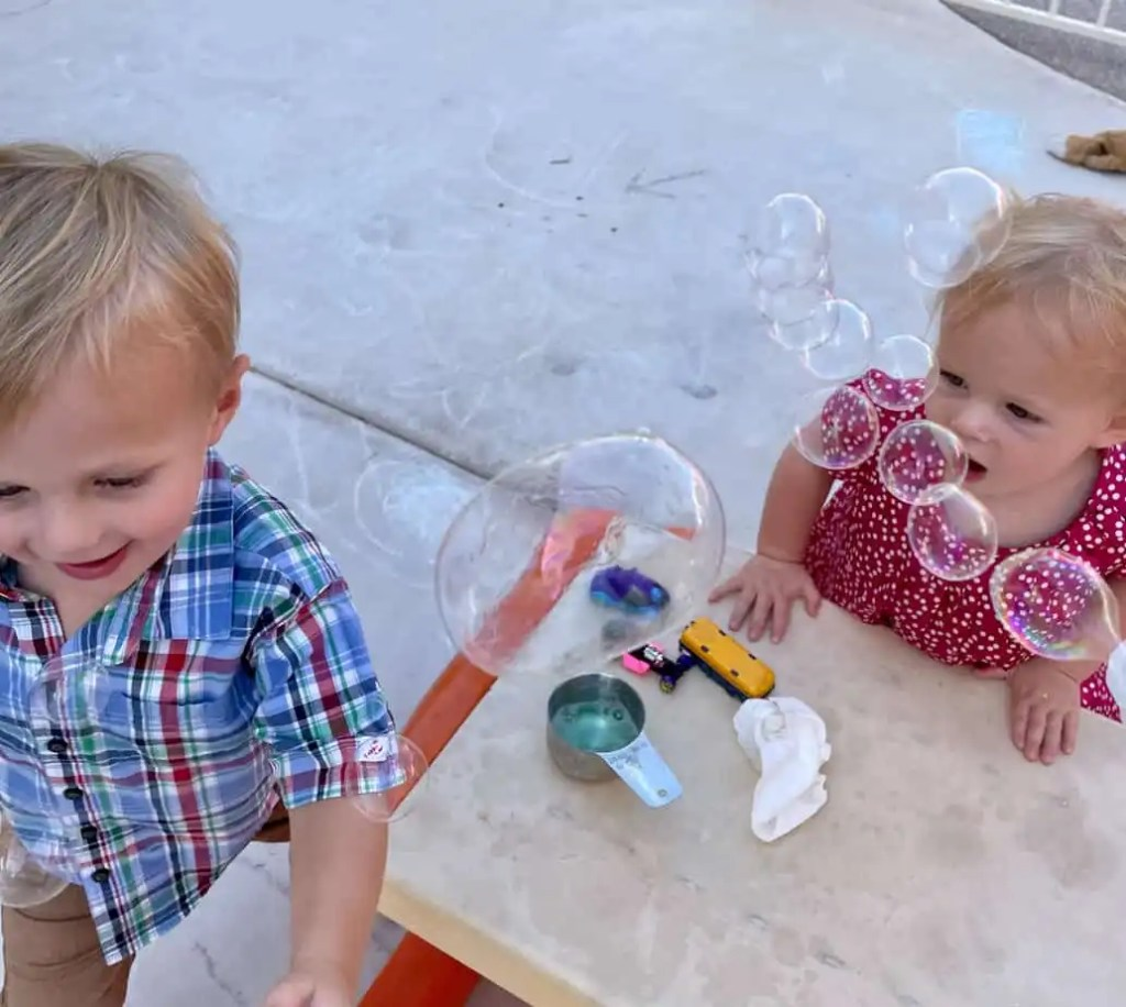 Two young kids playing with bubbles and smiling