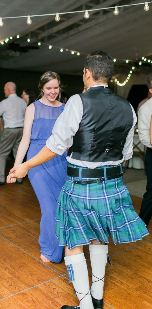 Image of a man in a kilt dancing with a woman. The kilt is beginning to flow upwards with the movement.