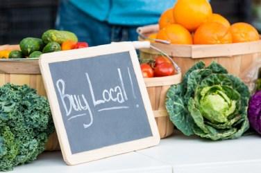 Fresh farmers market veggies with buy local chalkboard sign